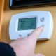 A person lowers temperature on a home thermostat. Enegry saving concept
