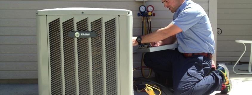 Albuquerque HVAC tech kneeling and repairing outdoor HVAC unit.